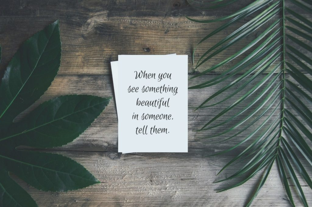 A green leafy background setting with a quote about complimenting someone written on a piece of paper.