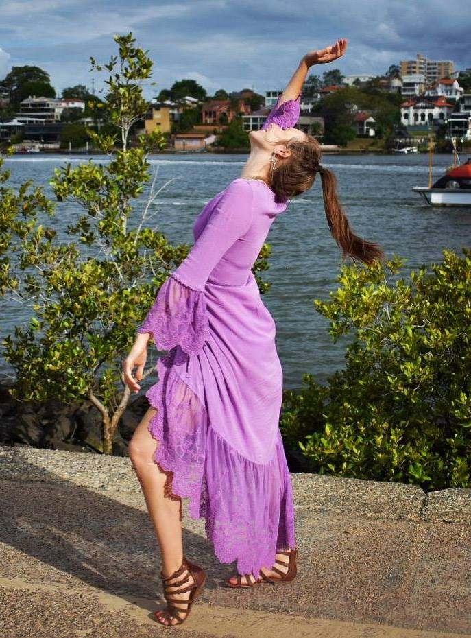A picture of me looking to the light, wearing a favourite bright purple dress that reminds me of warmth and happiness. This is my positive, fun, open, free self being me.